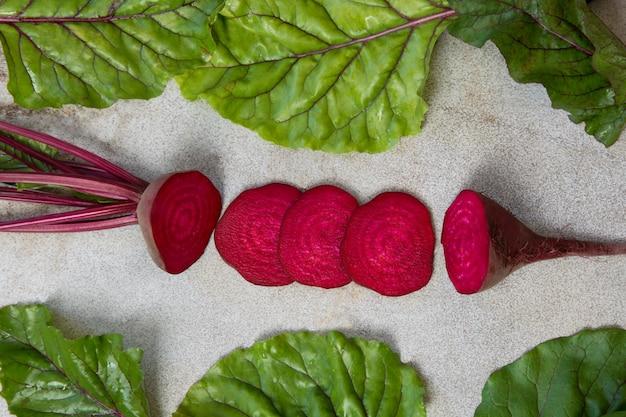 Сырцовые свекла отрезанные с листьями на деревенской доске. вид сверху, скопируйте пространство.