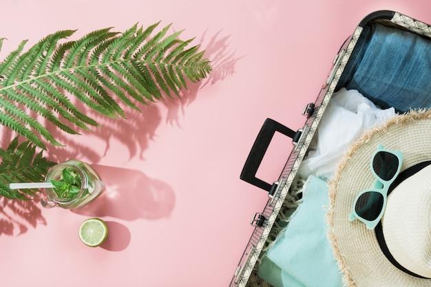 Лист папоротника, тропическая вода детокс и открытый чемодан с одеждой на пастельно-розовый.