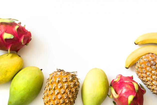 孤立したトロピカルフルーツ。パイナップル、バナナ、ドラゴンフルーツ、マンゴー白で分離。上面図。