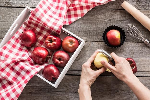 木の板に白樺の箱で熟した赤いリンゴ。女性は特別なナイフ、台所用品を調理するためのりんごをむきます。