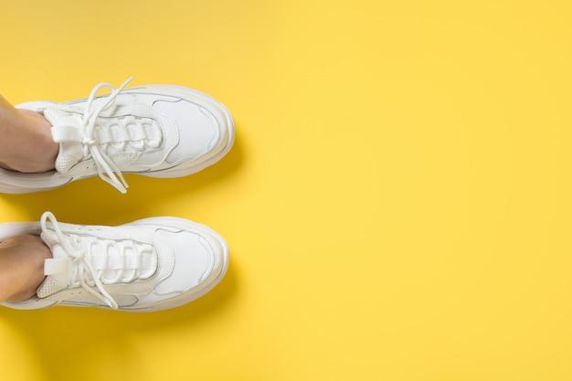 Пара белых женских кроссовок на желтом. плоская планировка, вид сверху минимальный.
