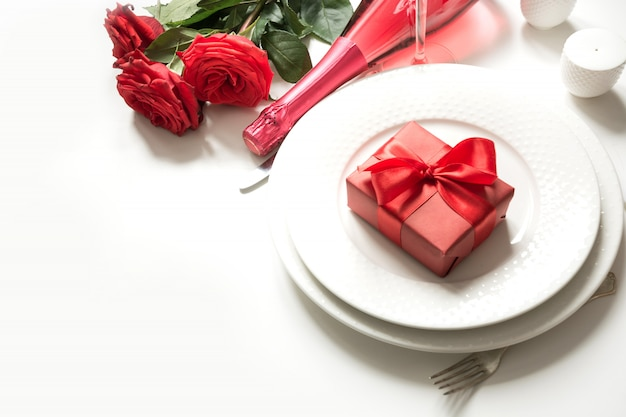 バレンタインデーや誕生日の夕食。シャンパンと赤いバラの優雅さのテーブルセッティング。