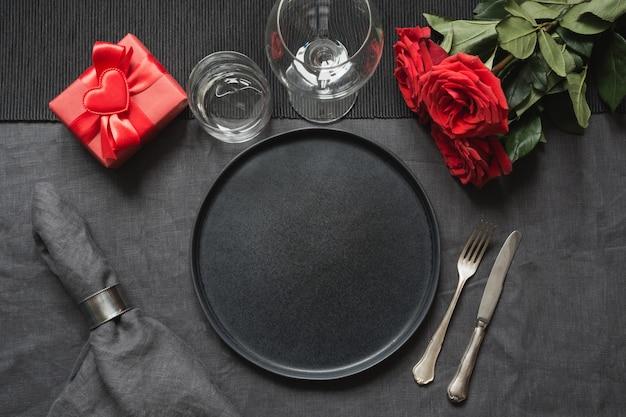 バレンタインデーや誕生日の夕食。黒いリネンのテーブルクロスの上の赤いバラとエレガンステーブルの設定。