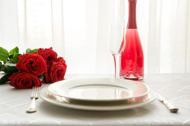 赤いバラとシャンパンバレンタインデーのテーブルの場所の設定。日付への招待状。