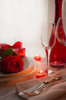 Урегулирование места стола дня святого валентина с красными розами и шампанским. приглашение на свидание.