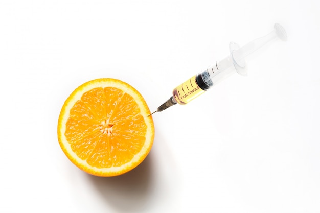 オレンジ色の果物とプラスチック製の使い捨て注射器。ラウンドスライスを白で隔離されます。閉じる。