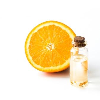 Долька апельсина и бутылка с маслом или эссенцией. круглый ломтик, изолированные на белом. закройте