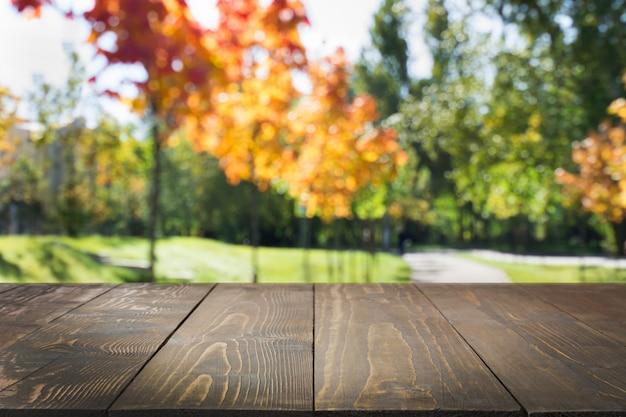 Естественный абстрактный конспект осени с деревянной столешницей для дисплея вашего продукта