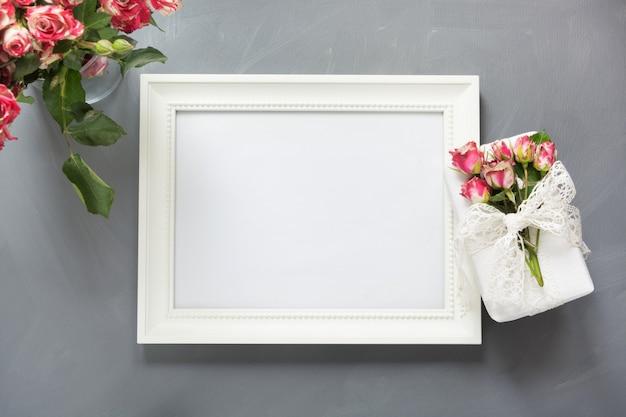 女性の贈り物と灰色の上の小さなバラの白いフォトフレーム。上面図。スペースをコピーします。