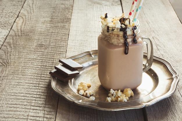ホイップクリームとチョコレートのコーヒーミルクセーキは、木製のテーブルの上の石工の瓶で提供しています。