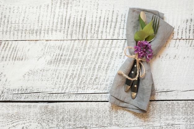 白い木製のテーブルにカトラリーとライラックの花で春のお祝いテーブルの設定。スペースをコピーします。