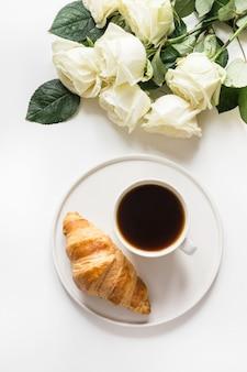 一杯のコーヒーと焼きたてのクロワッサン。上面図。スペースをコピーします。