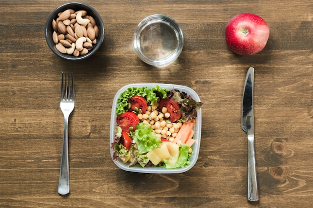 木製のテーブルの上のコンテナーでオフィスランチの野菜サラダ。コンセプト健康的な栄養。弁当箱。