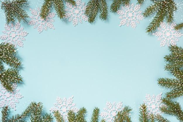 雪の結晶と青色の背景に枝のクリスマスフレーム