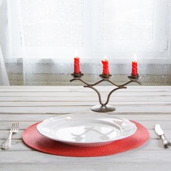 Урегулирование праздничного стола с белой посудой и красными свечами.