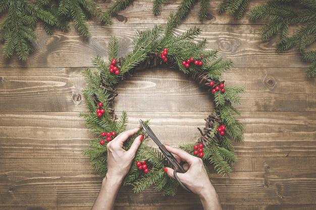 新鮮ですべての天然素材を使用してクリスマスリースを作る。