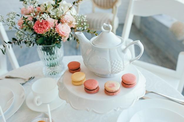 創造的な春の組成。エレガントな甘いデザートマカロン、紅茶またはコーヒーカップ、美しいパステルカラーのベージュと白い大理石のサンゴの花の花束