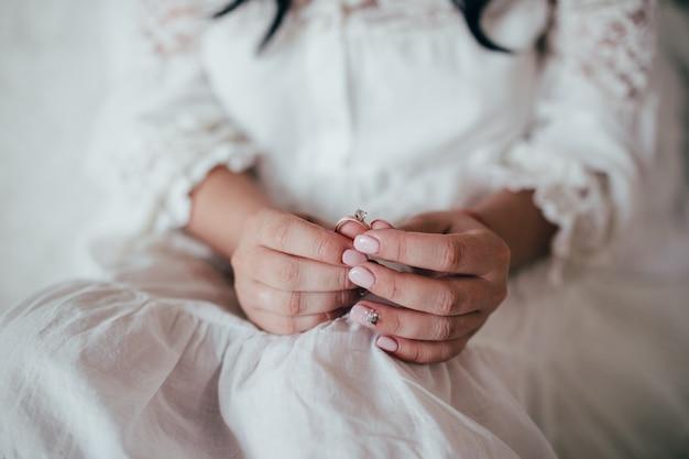 花嫁は結婚式のダイヤモンドリングを手に保持します