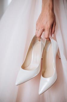 ウェディングドレスを着た花嫁は、スタイリッシュなベージュの靴を手に持っています。