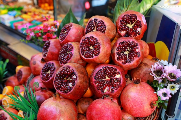 オレンジ、グレープフルーツ、ザクロのスライス。フルーツ。熟したジューシーなザクロ、みかん、オレンジはイスタンブール通りの果物屋のカウンターで販売されています。