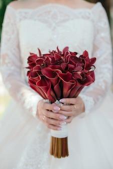 花嫁は彼女のオランダカイウウェディングブーケの花を保持