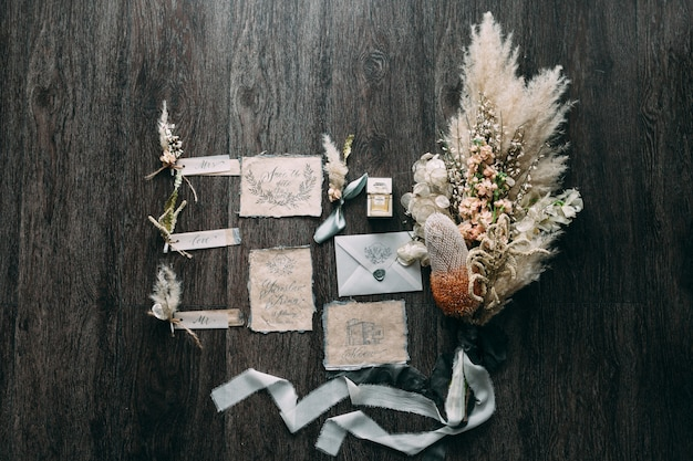 Свадебный букет в деревенском и графическом стиле с красивыми каллиграфическими карточками с цветочными и шифоновыми бобинами. красивое свадебное приглашение. вид сверху.