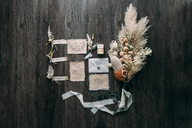 木製のテーブルに花とシフォンのボビンと美しい書道カードのウェディングブーケ素朴でグラフィックアート。美しい結婚式の招待状。上面図。
