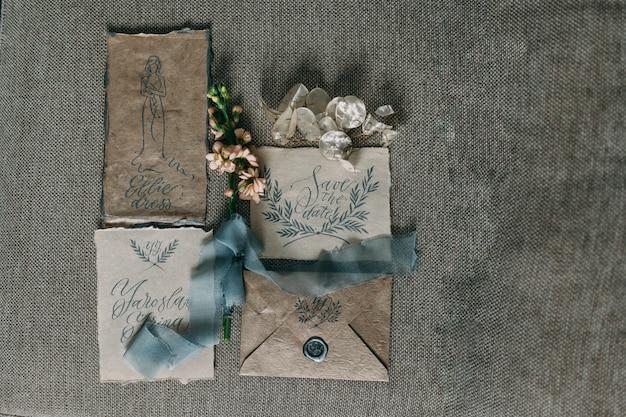 花とシフォンのボビンと美しい書道カードの結婚式の素朴でグラフィックアート。美しい結婚式の招待状。上面図。