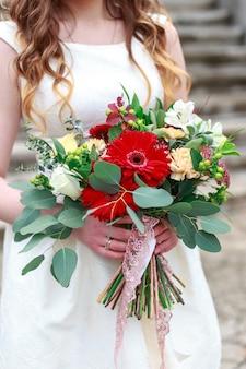 Свадебный букет цветов, в том числе красный гиперикум, розы, ландыши, мини-розы, сеяный эвкалипт, астильба, скабиоза, пиерис и плющ