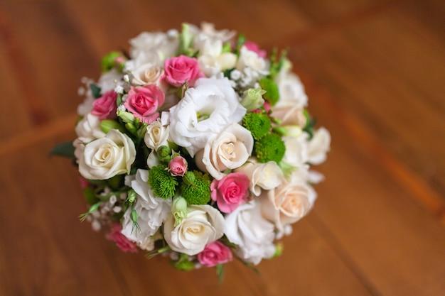 赤いセイヨウオトギリソウ、バラ、スズラン、ミニローズ、シードユーカリ、アスチルベ、スカビオサ、ピエリス、ツタを含む花のウェディングブーケ