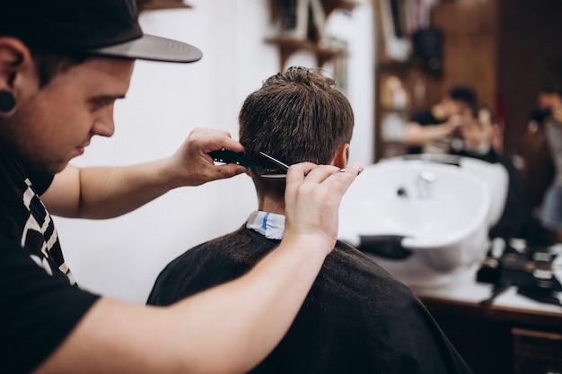 Мастер стрижет волосы и бороду мужчины в парикмахерской, парикмахер делает прическу для молодого человека