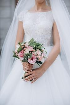 赤、ピンク、白の花、バラ、ユーカリ、牡丹、オランダカイウユリの美しいウェディングブーケ