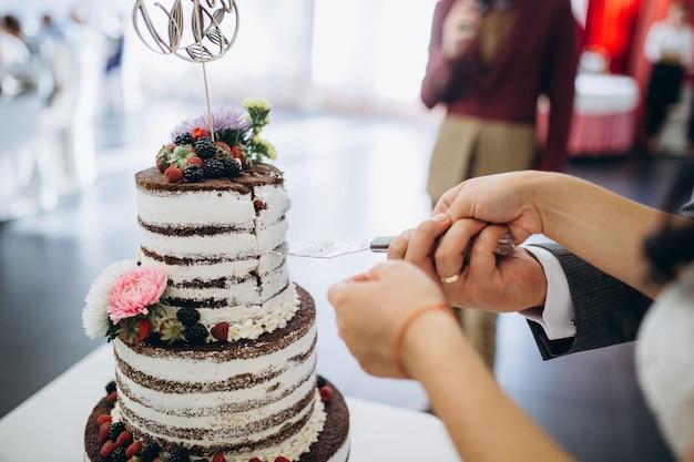 新郎新婦が美しいウェディングケーキを切っています。素敵な光。結婚式のコンセプト