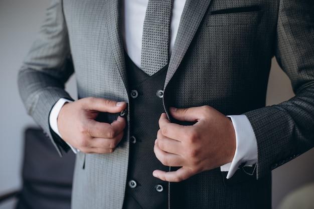 ジャケットをボタンモダンなフォーマルな服に身を包んだ若いハンサムなスタイリッシュな男。灰色のジャケット、紫のシャツの男の手のクローズアップ。結婚式のお祝いや卒業の準備ができている人。
