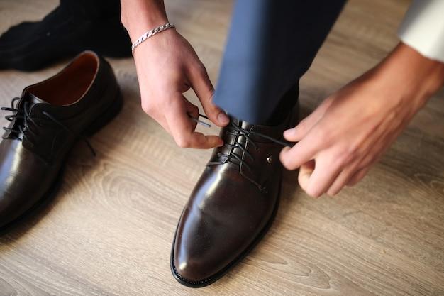 Крупным планом человека в рубашке наряжаться и регулировать галстук на шее в домашних условиях