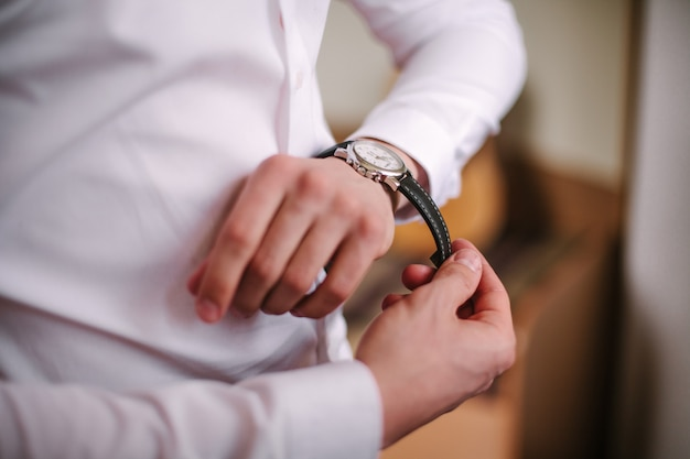 実業家は彼の腕時計で時間をチェック