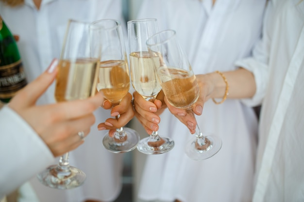 Веселые женщины чокаются бокалами шампанского на вечеринке
