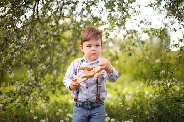 晴れた日に草の上の夏の公園で木製の飛行機で遊ぶかわいい金髪の少年、子供に焦点を当てる