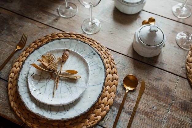 白い皿とスプーン、フライパン用器具、結婚式の装飾と黄金のフォーク。