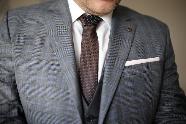灰色のスーツで自信を持って鋭い服を着た男