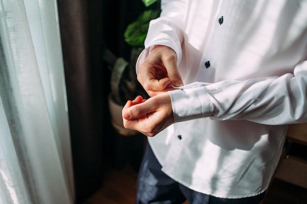 ドレスアップと自宅の首にネクタイを調整するシャツの男のクローズアップ。
