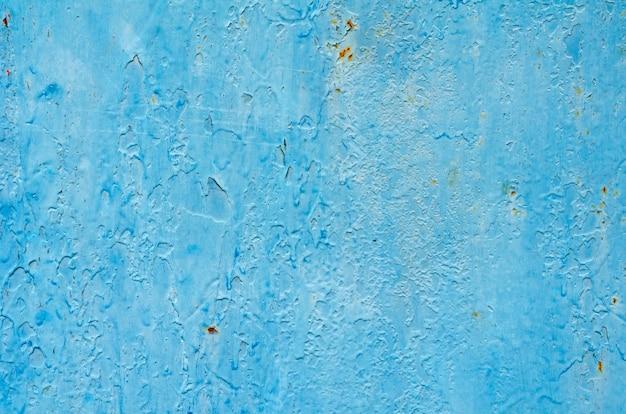 ペイントの多くの層とビンテージブルーとターコイズブルーの塗られた鉄の壁の背景のテクスチャ