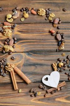 コーヒー豆、レーズン、ナッツ、シナモン、テキストのコピースペースを持つ自然な木製の背景のフレーム