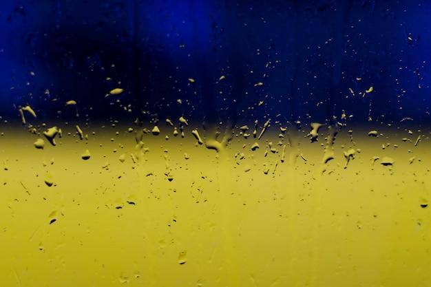 ウクライナの国旗の色の青と黄色の背景に、窓からすに雨滴