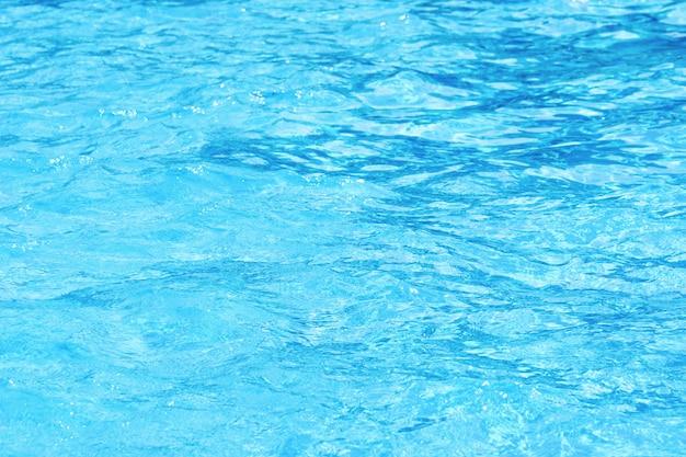 ホテルのスイミングプールできれいな青い波状水の背景