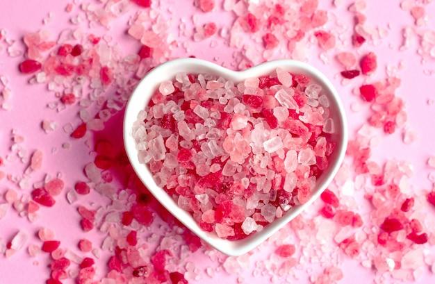 ハート形の受け皿にピンクの紙の背景にヒマラヤピンクの塩