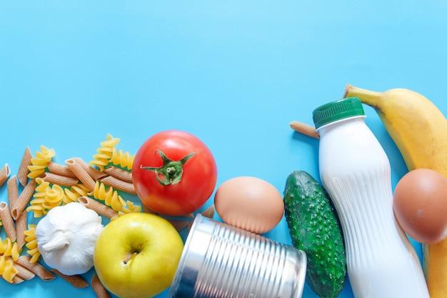 食料供給、青色の背景に隔離期間の危機の食料ストック。パスタ、トマト、缶詰、キュウリ、リンゴ、バナナ、ニンニク。