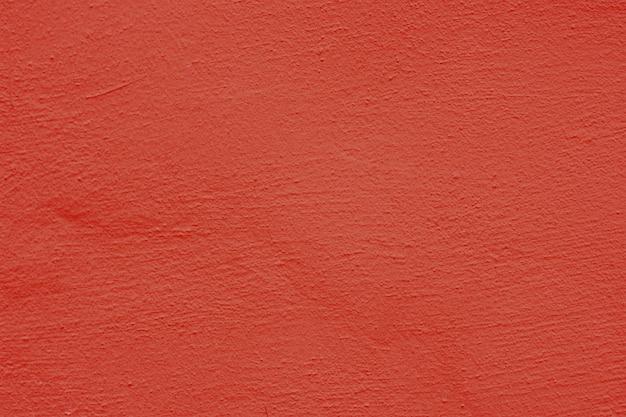 赤い漆喰の背景に塗られ、塗られた外装、セメントの粗いキャストとコンクリートの壁の質感