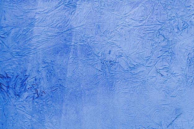 青い漆喰の背景に塗られ、塗られた外観、セメントの粗いキャストとコンクリートの壁の質感