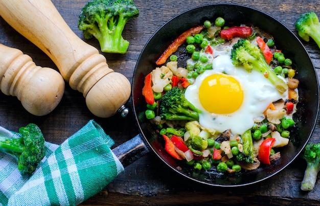 目玉焼きと野菜の混合物でフライパン:ピーナッツ、ブロッコリー、パプリカ、冷凍ブロッコリー